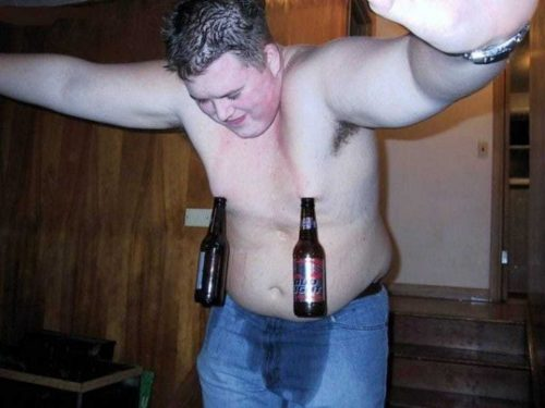 Shirtless overweight man with beer bottles hanging from nipples.