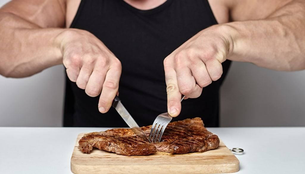 Bodybuilder Eating Steak While Following the Vertical Diet