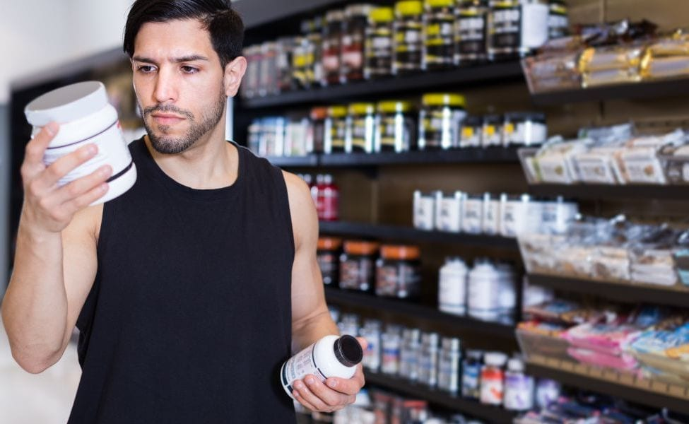 Man choosing between supplements at nutrition store.